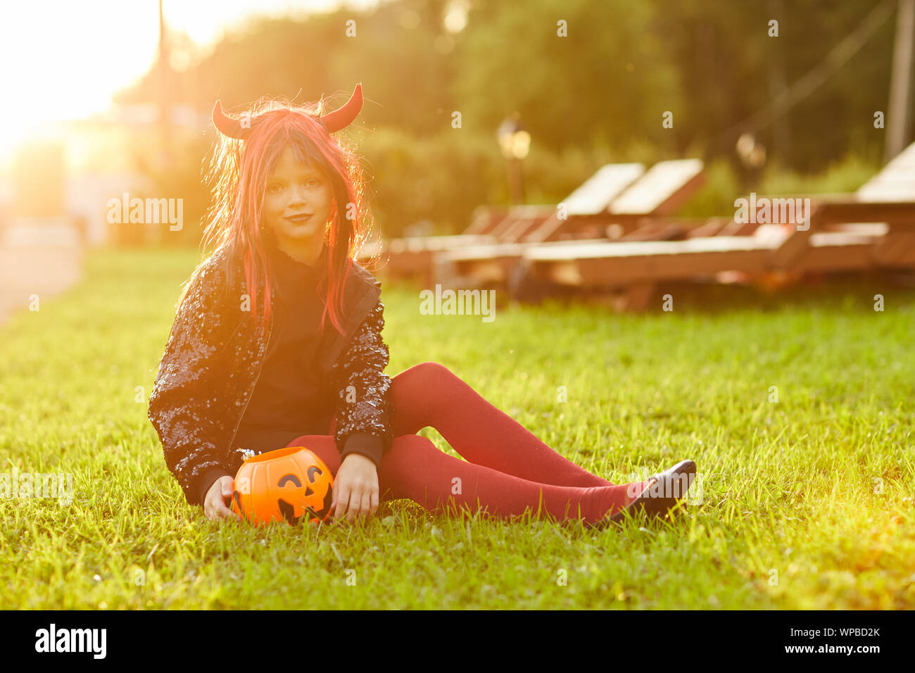 Full length portrait of cute little girl wearing Halloween costume sitting on green lawn with pumpkin basket and looking at camera, copy space Stock Photo