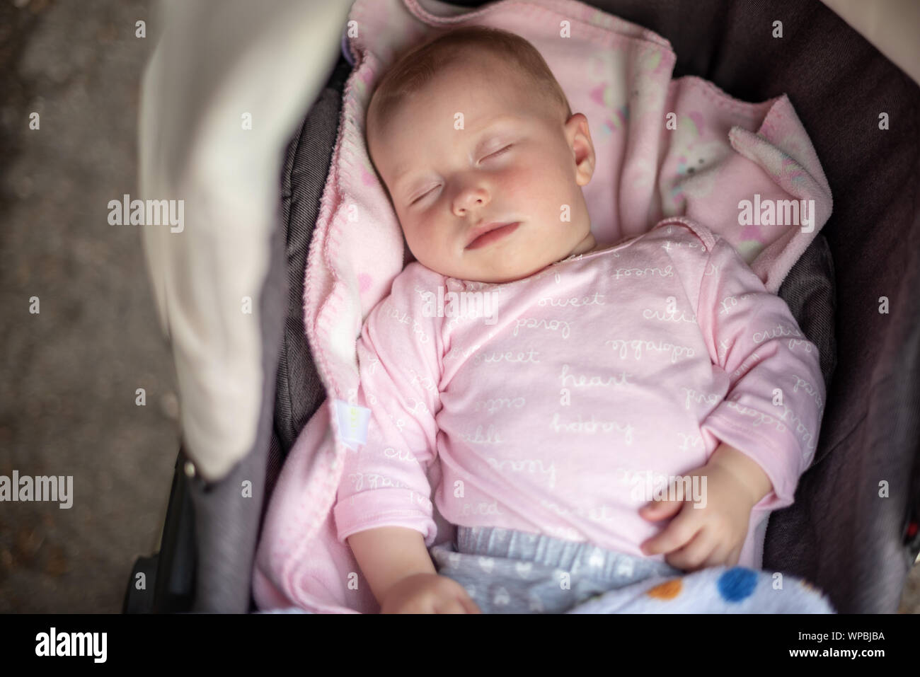 Baby sleeping in a baby carriage in the air. Stock Photo