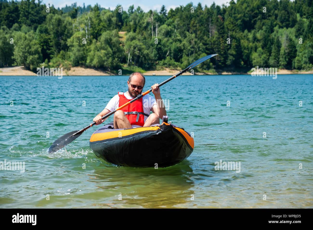Man paddling in inflatable kayak on lake Lokve, in Gorski kotar, Croatia. Adventurous kayaking experience in a beautiful nature. Stock Photo