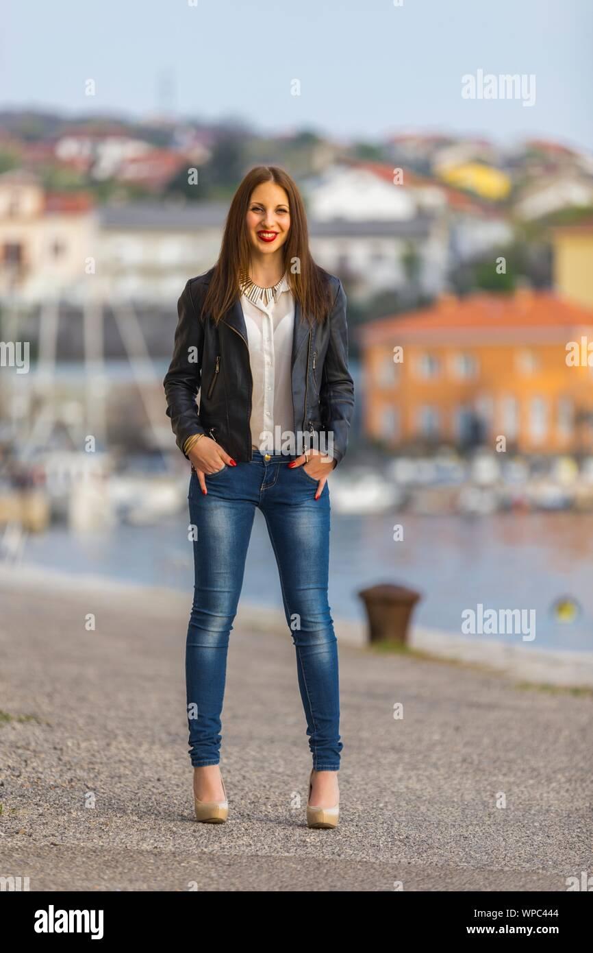 Teen girl in denim pants Beige high-heels standing on seaside hands fingers in pockets looking at camera eye eyes-contact eyeshot smiling Red-lips Stock Photo