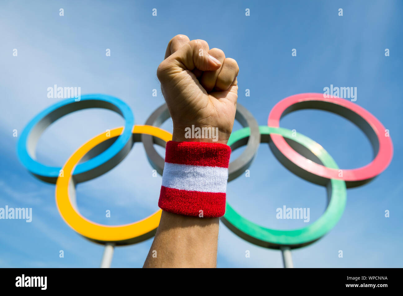 RIO DE JANEIRO - MARCH 15, 2016: A hand wearing red and white Team Japan wristband punches the air in front of Olympic Rings. Stock Photo