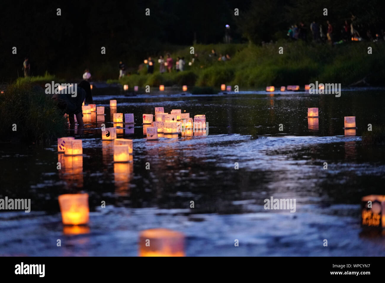 Many water Lanterns float downstream from people releasing them at Pamperin Park in Green Bay, Wisconsin Stock Photo