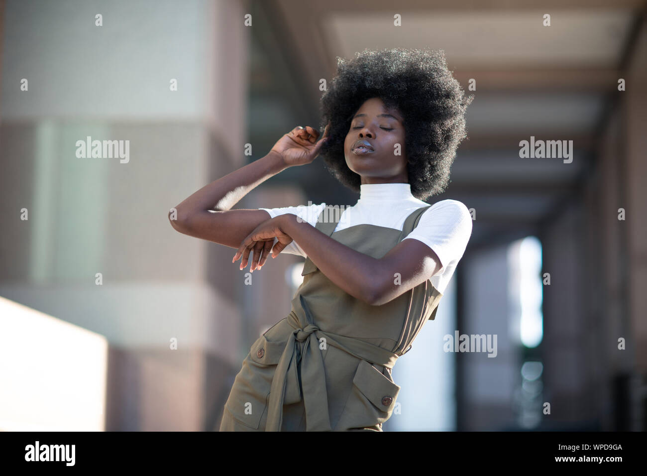 Fashionable African American girl in downtown wearing fancy overalls and white turtleneck Stock Photo