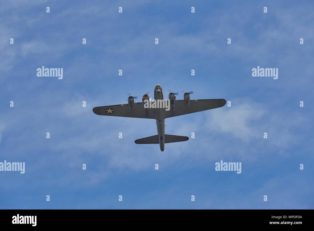 Under side view of the WWII bomber the Boeing B-17 Flying Fortress while flying over the top against a blue sky with some clouds Stock Photo