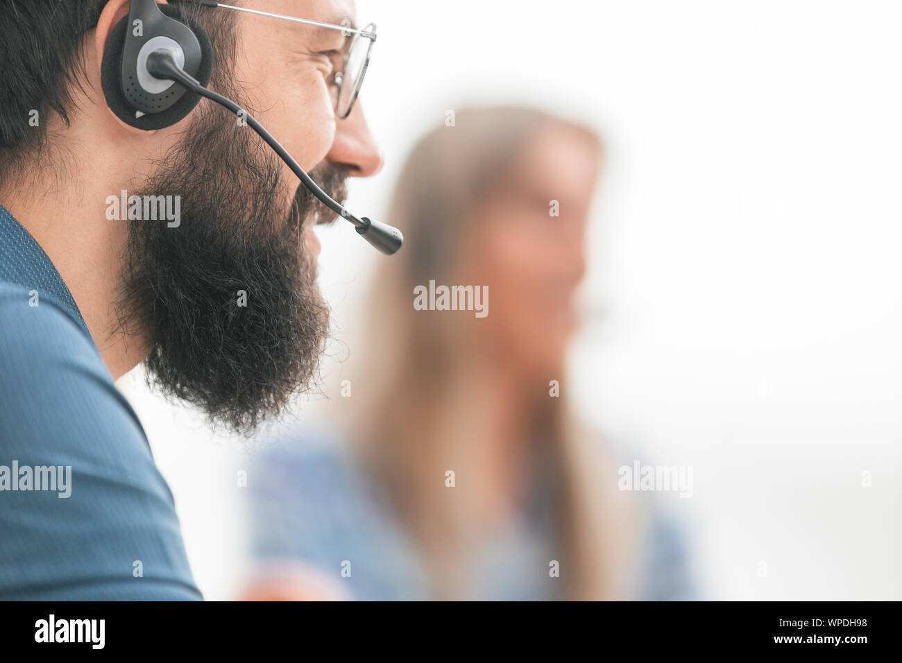 close up. smiling man in headset on blurred background Stock Photo