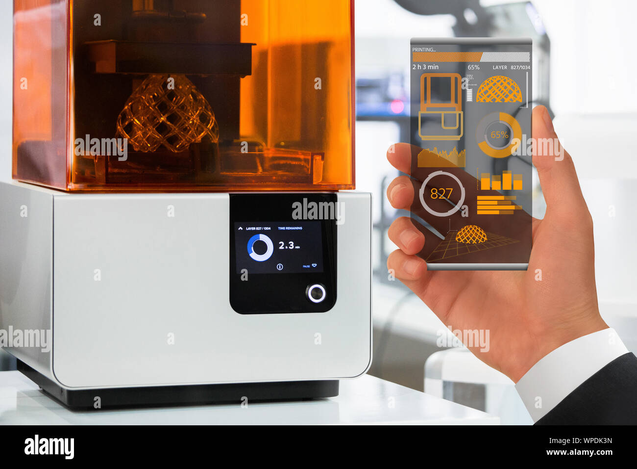 Hand with futuristic transparent smartphone. Application for control 3D printer in the laboratory. Stock Photo