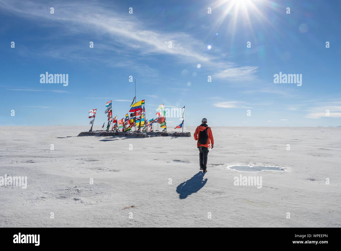 Young man walking to the international flags from different countries in Uyuni salt flat in sunny day with sun rays, Bolivia, South America travel voc Stock Photo
