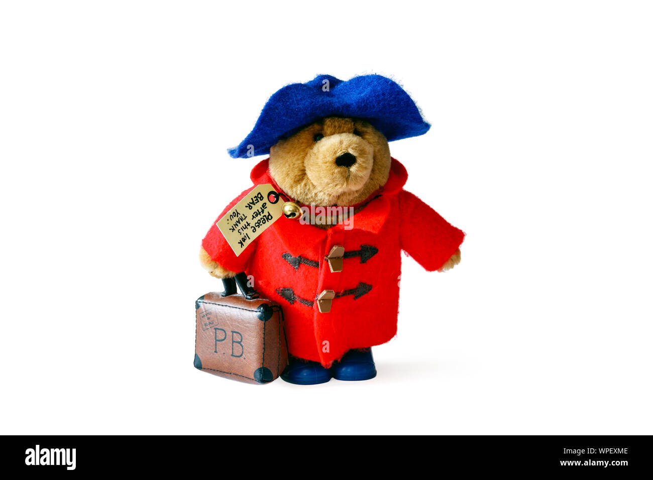 A Paddington Bear soft toy with red duffel coat, blue hat and suitcase, isolated against a white background Stock Photo