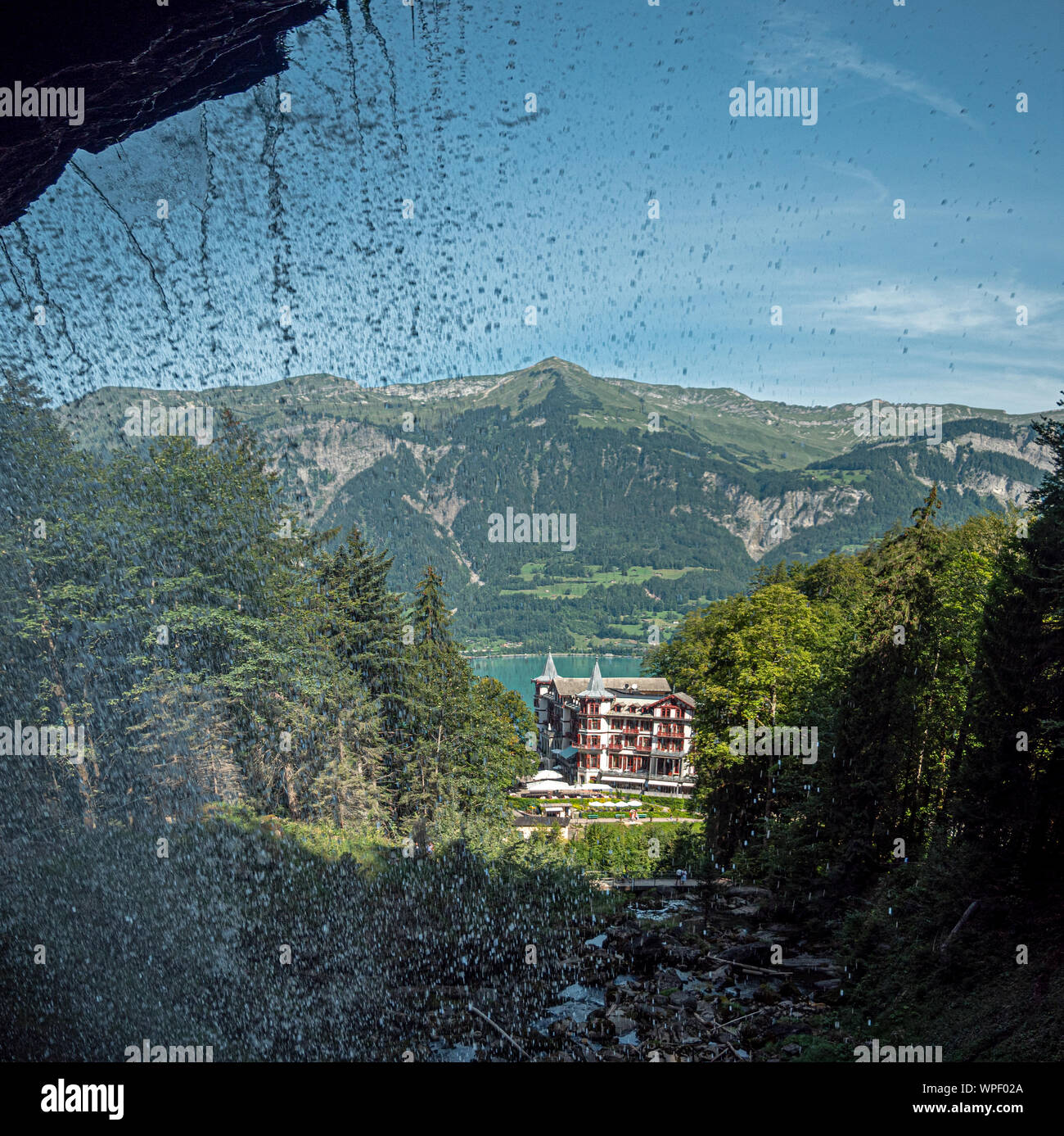 a Postcard photo of the Giessbach falls and hotel in central switzerland. Taken from perspective of  behind the waterfalls as the water falls in front Stock Photo