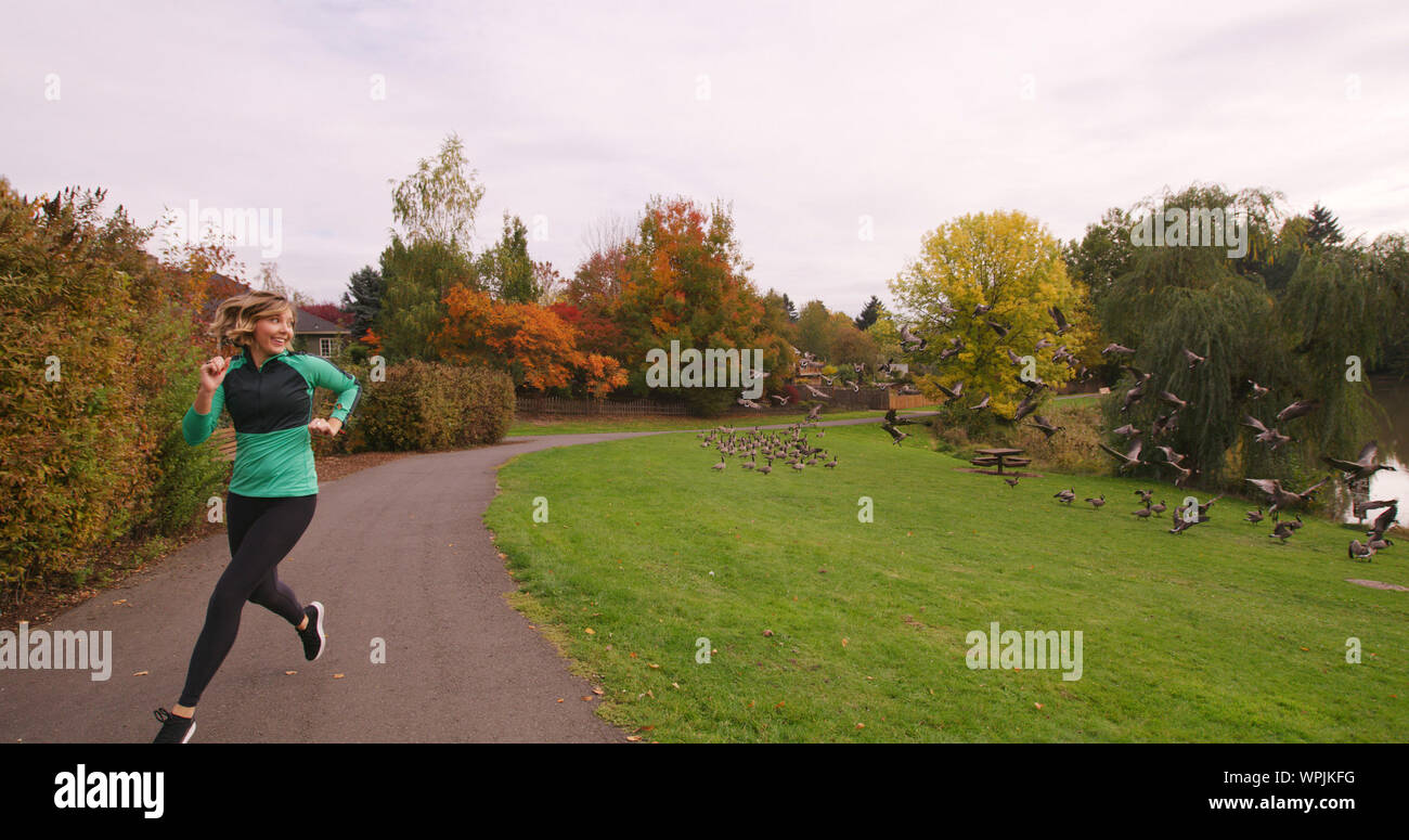 Young Woman On Running On Road By Field Against Sky Stock Photo