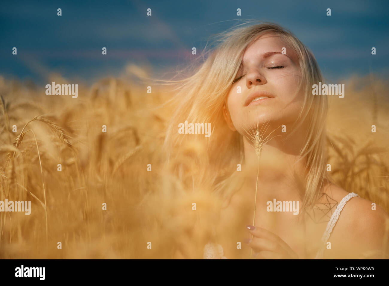 nature, summer holidays, vacation and people concept - face of happy smiling woman or teenage girl n in hat on cereal field Stock Photo