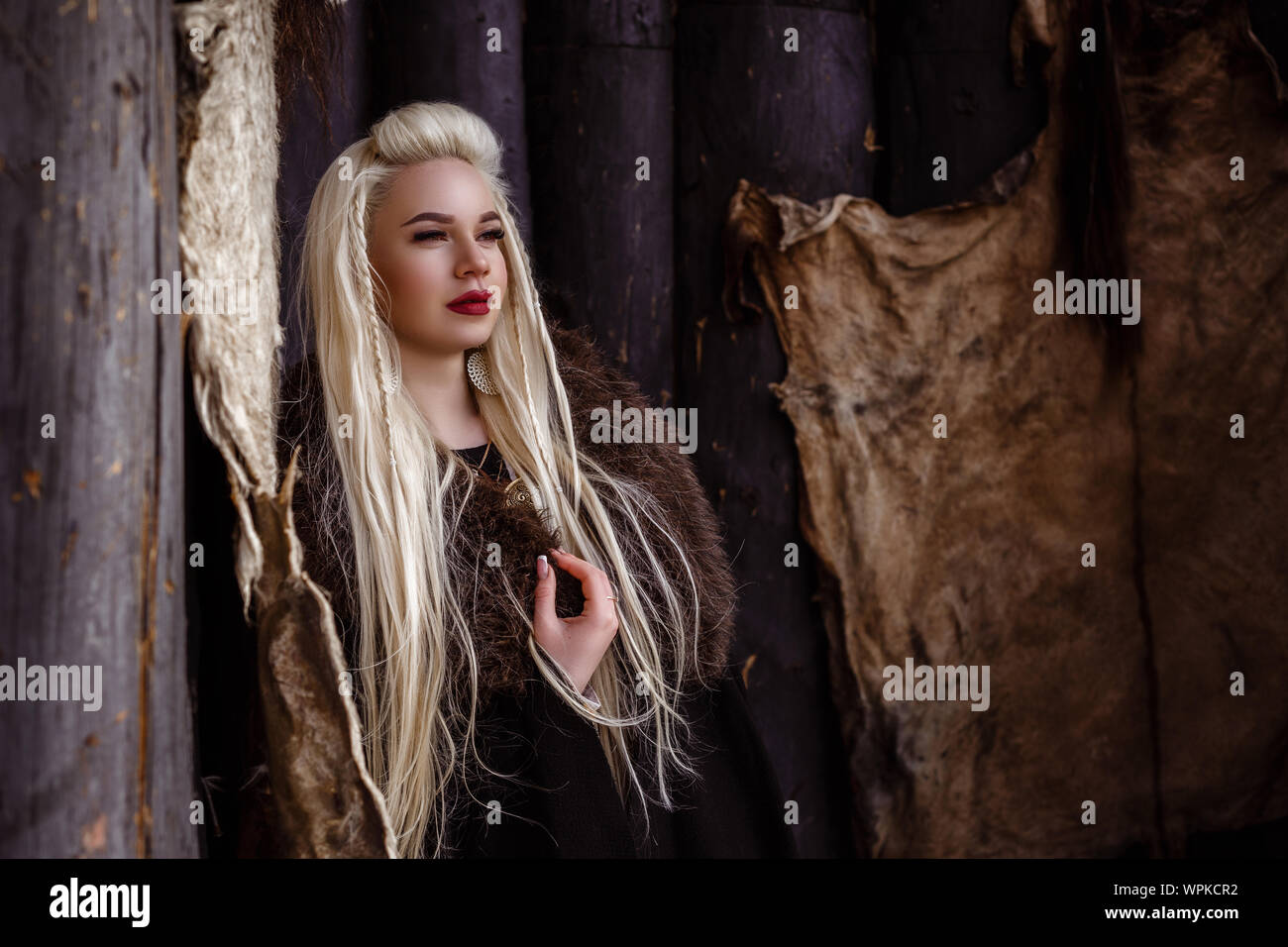 Outdoors portrait of beautiful furious scandinavian warrior ginger woman in a traditional clothes with fur collar, with sword in her hand and wooden V Stock Photo