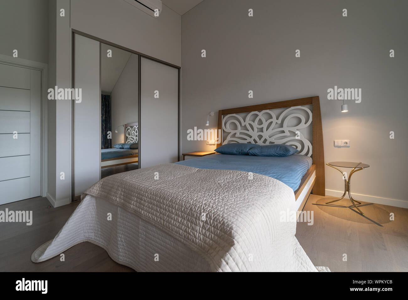 Main Bedroom With Big Original Bed Bedside Tables Lamps On The Wall And Mirror Wardrobe In The Modern House Stock Photo Alamy