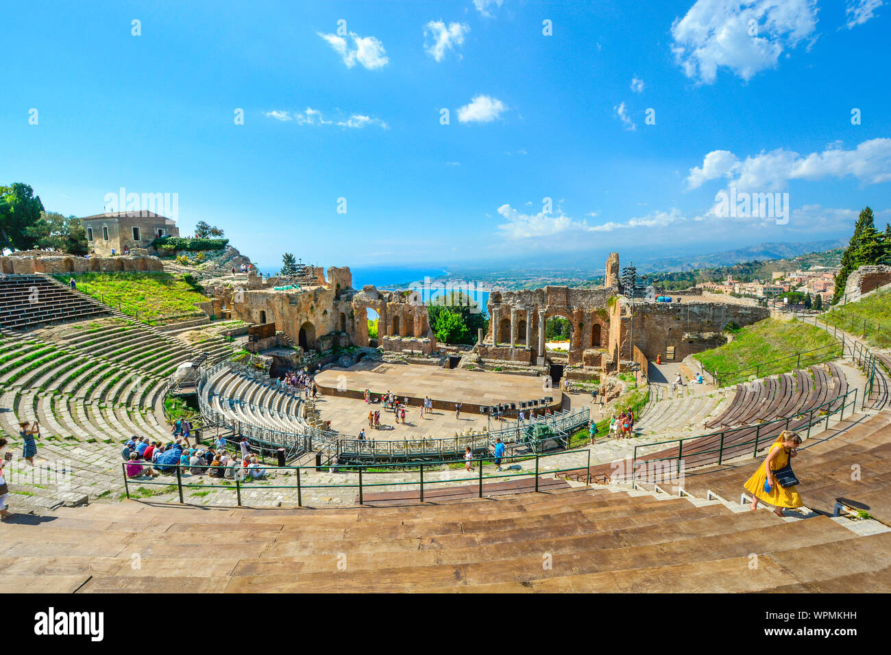 A woman walks up the ancient stairs at the Greek Theatre in Taormina, Italy on the Italian island of Sicily. Stock Photo