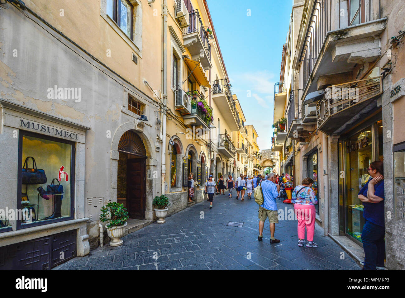 A couple window shops on the Corso Umberto street in the historic Taormina old town on the island of Sicily, Italy in the Mediterranean. Stock Photo