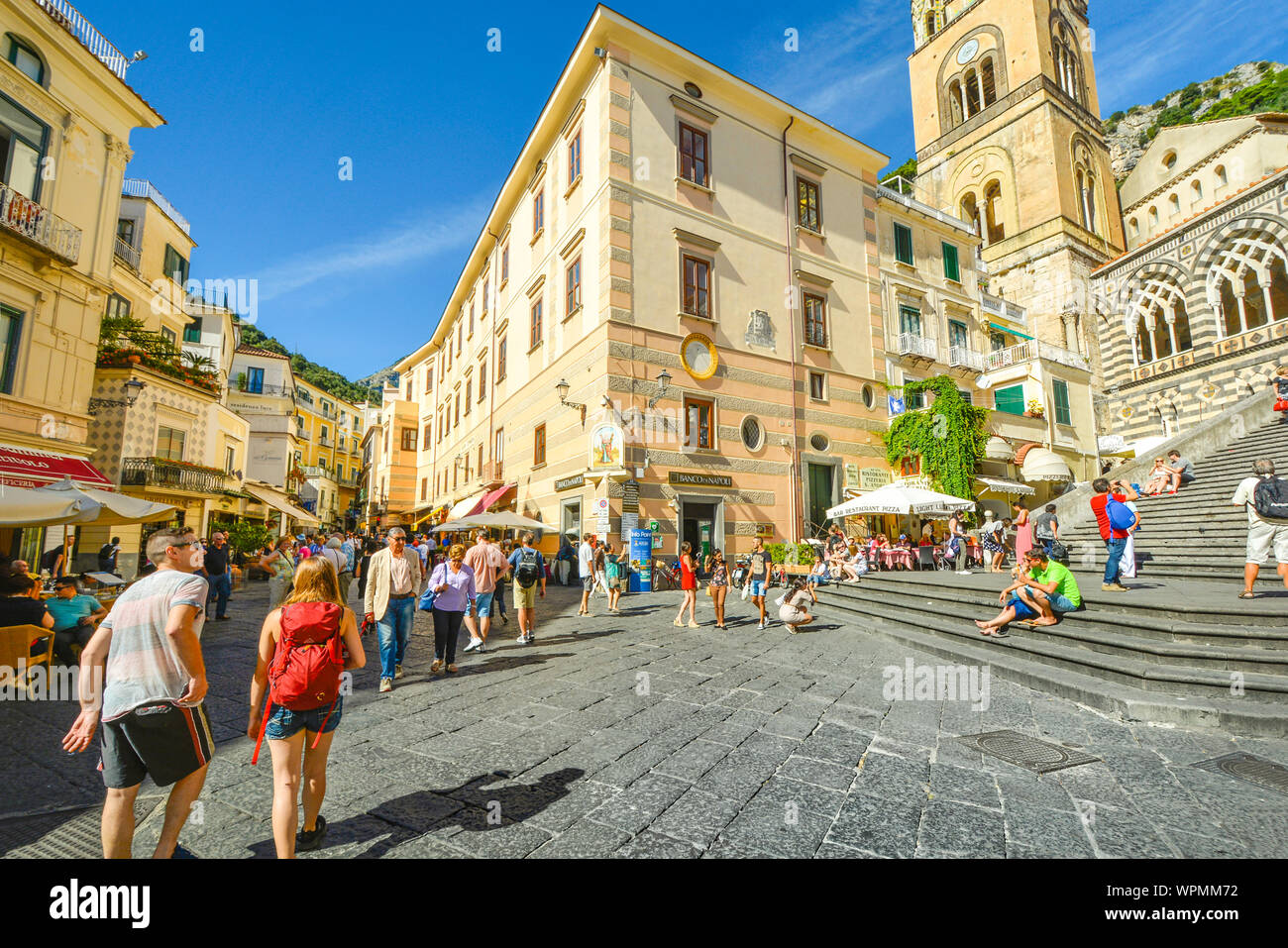 The center of the town of Amalfi on the Amalfi Coast of Italy with the stairs leading up to the famous Amalfi Cathedral as tourists shop and dine Stock Photo