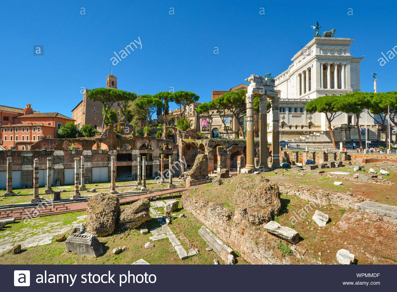 Ancient ruins near the Forum in Rome Italy with the Vittorio Emanuele Monument in the background on a sunny summer day Stock Photo