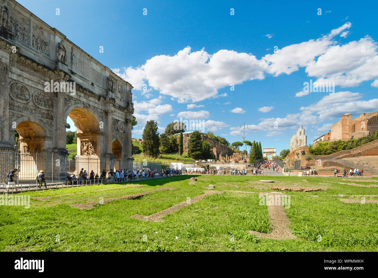 Tourists visit the Roman Forum, with the Arch of Constantine and Arch of Titus in view in Rome, Italy. Stock Photo