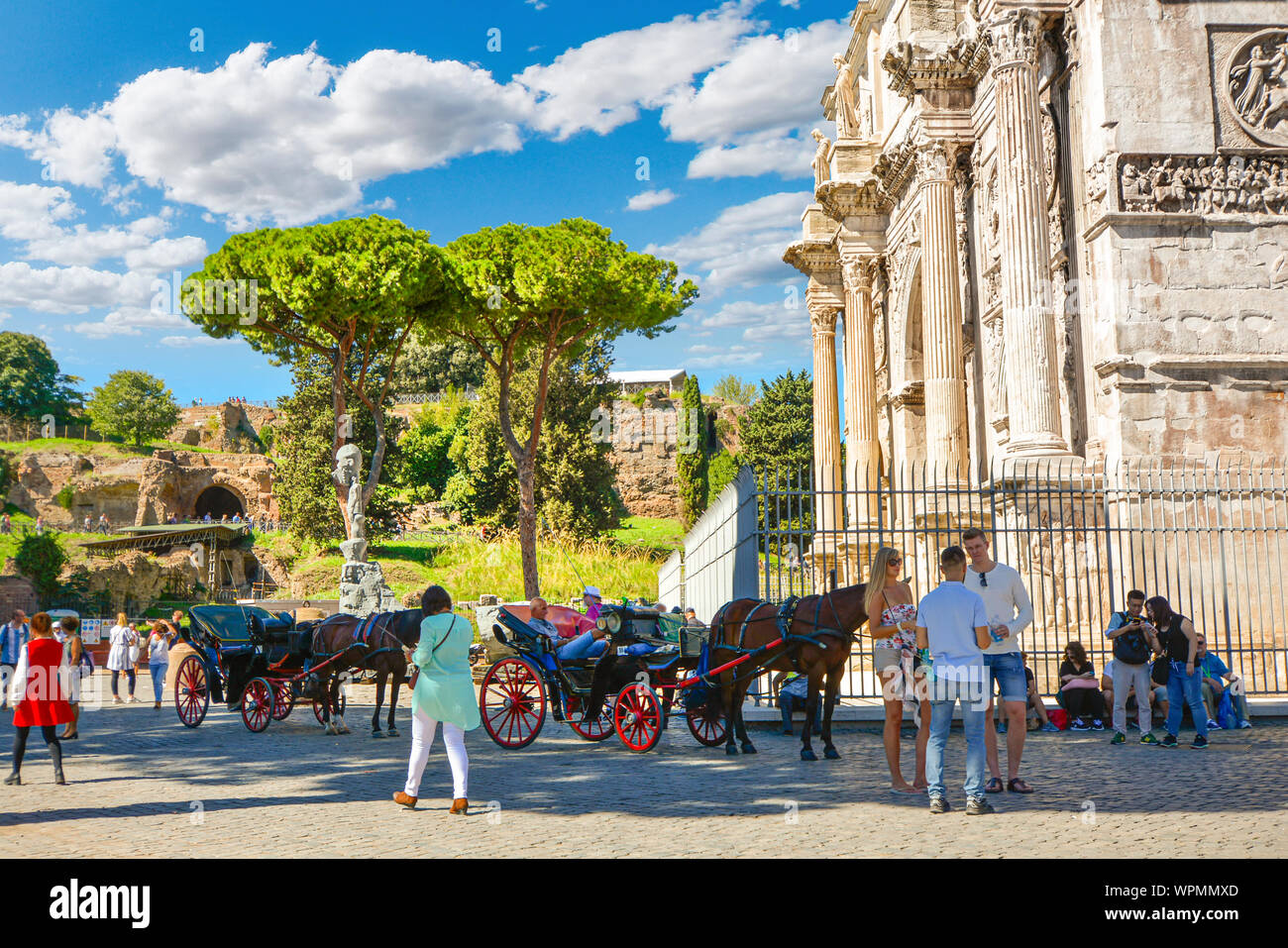 Tourists at the Arch of Constantine near the Colosseum and the Roman Forum with Capitoline Hill in the background as horse and carriages wait for hire Stock Photo