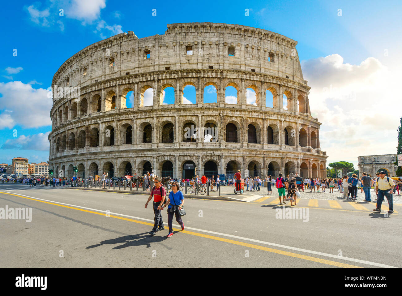 The ancient arena, the Colosseum of Rome in Italy on a summer day with tourists walking across the Via dei Fori Imperiali Stock Photo