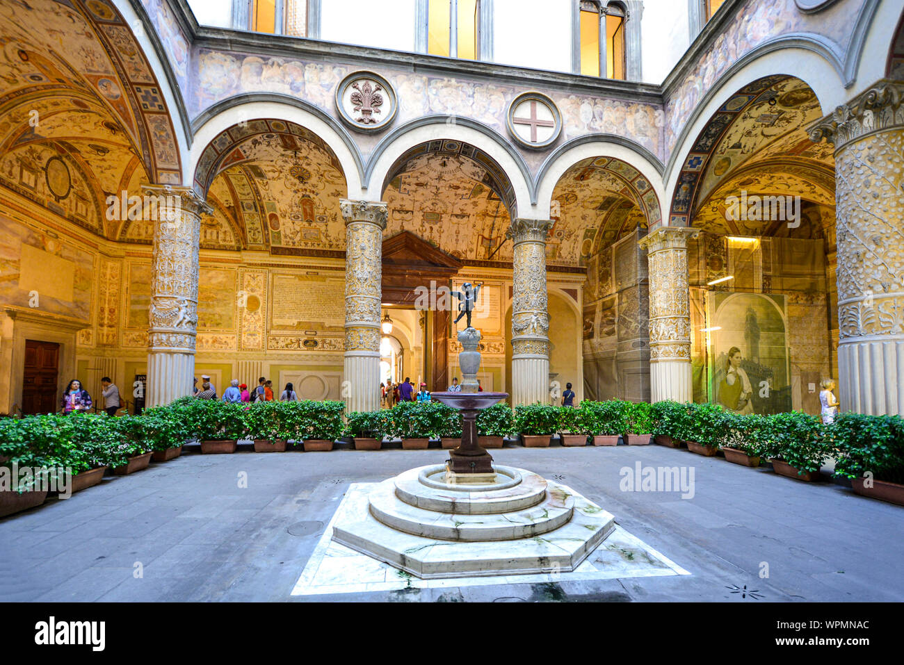 tourists visit the first courtyard of the Palazzo Vecchio in Florence Italy with a small fountain with statue, frescoes on the wall and vaulted column Stock Photo