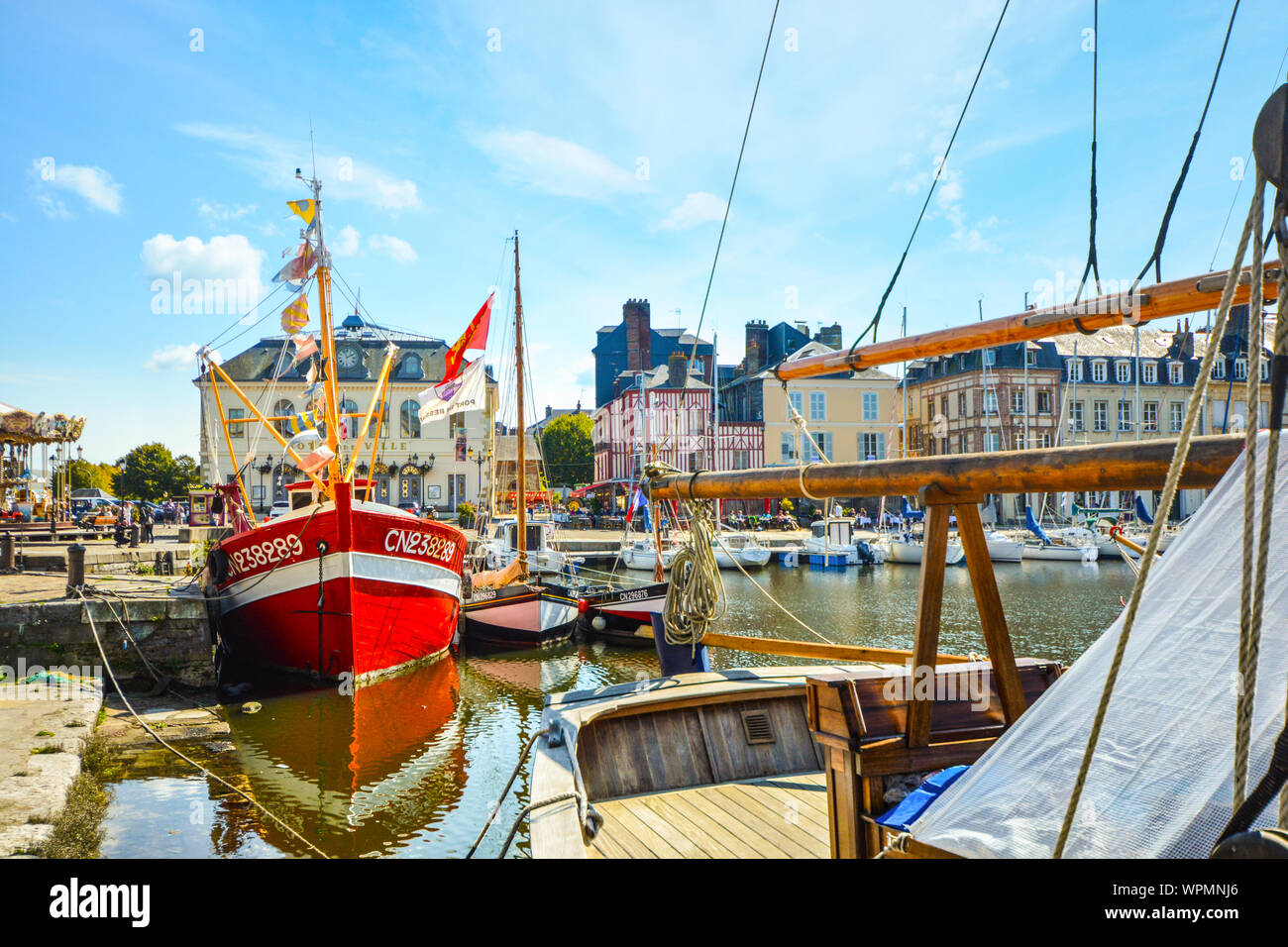 A red fishing boat is moored in the Old Pier at the historic coastal fishing village of Honfleur, France, at the English Channel on the Normandy Coast Stock Photo