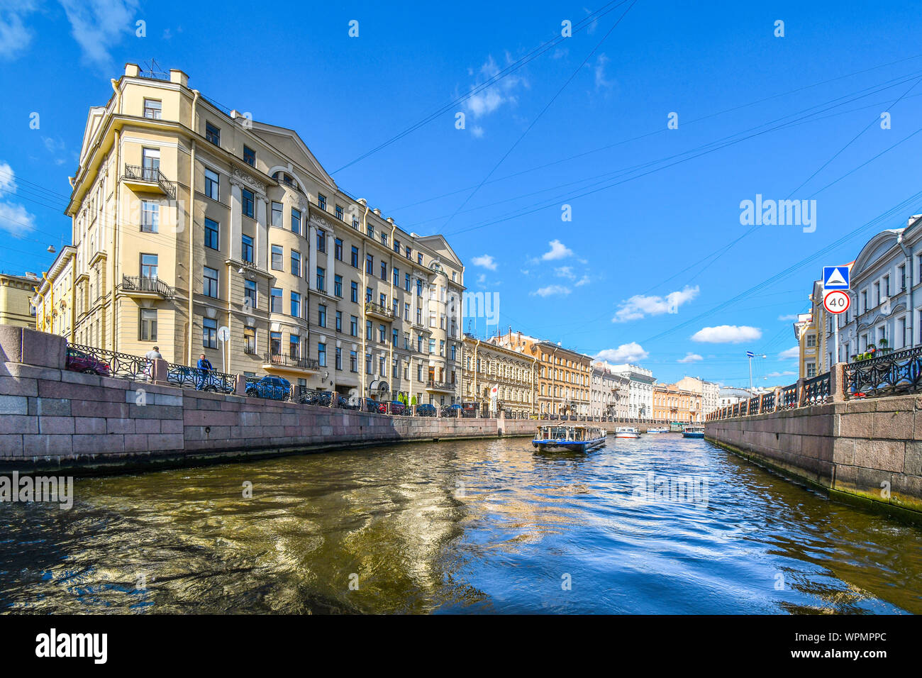 A tour boat cruises down one of the many canals in the historic center of St. Petersburg, Russia. Stock Photo