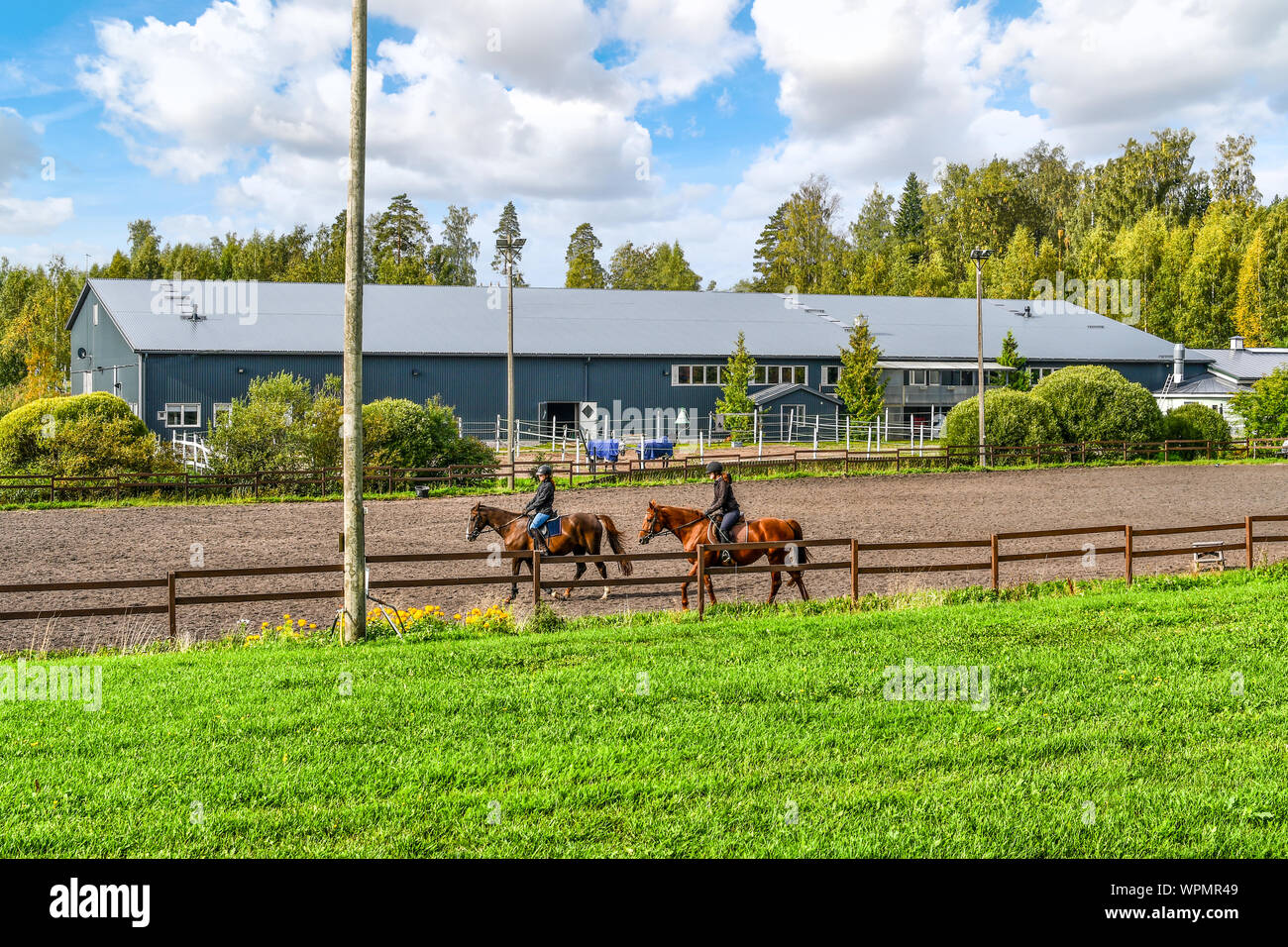Two female equestrians ride thoroughbred horses on a horse farm in front of a large indoor horse arena at the town of Sipoo Finland Stock Photo