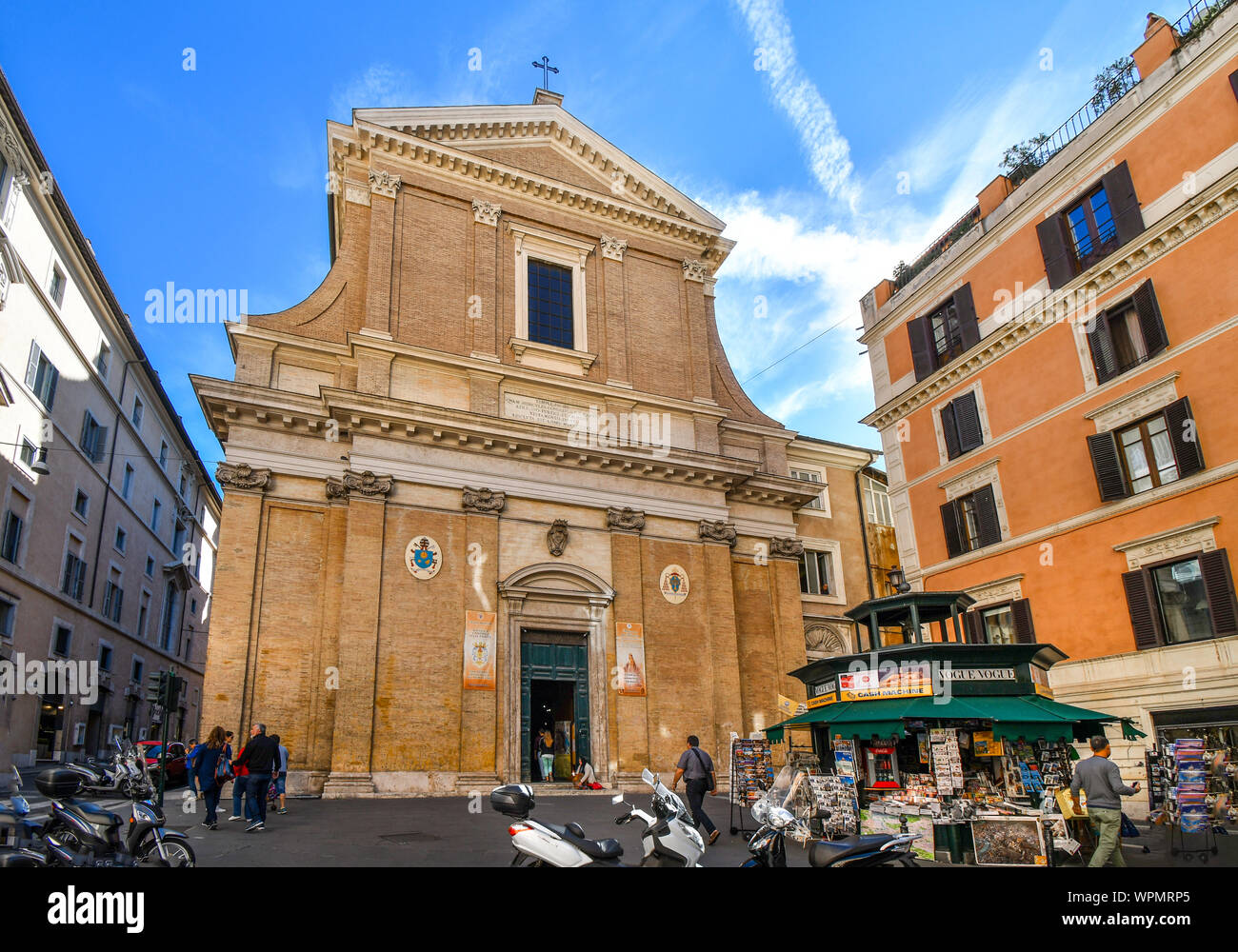 Tourists pass by a small news paper stand outside the Sant'Andrea delle Fratte church in the historic center of Rome, Italy. Stock Photo