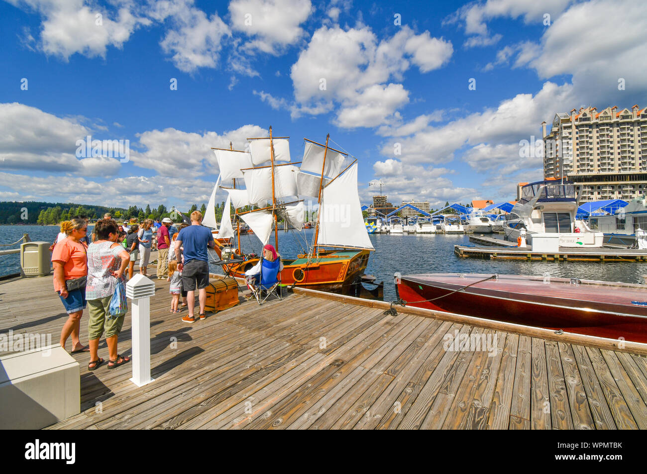 Visitors to the Coeur d'Alene Wooden Boat show talk with a boat owner dressed as a pirate about his miniature replica ship docked at the marina Stock Photo
