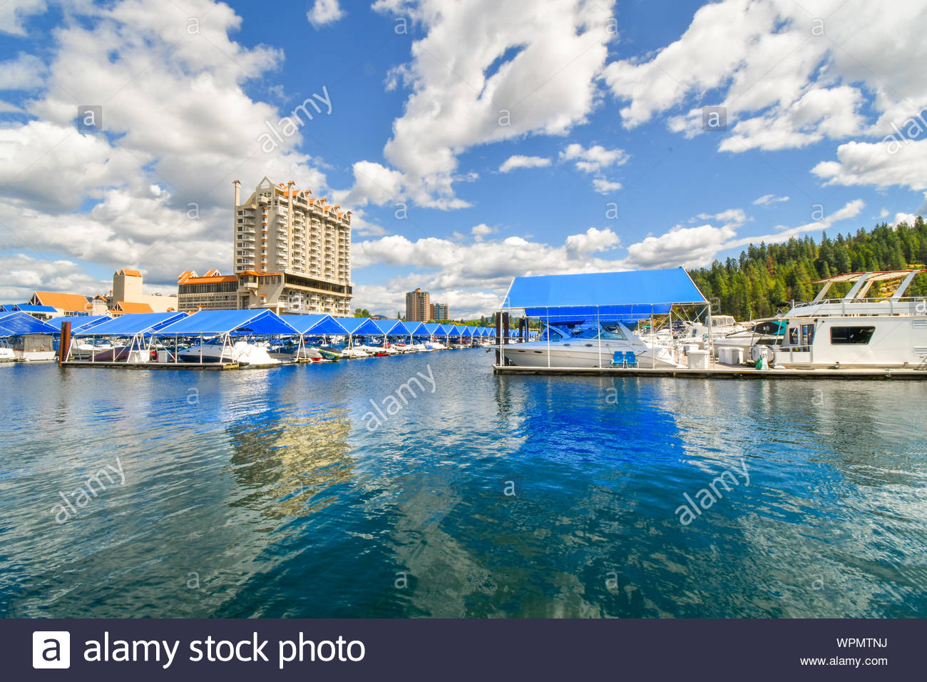 A view from the floating boardwalk of the marina full with boats and the Coeur d'Alene Resort on Lake Coeur d'Alene. Stock Photo