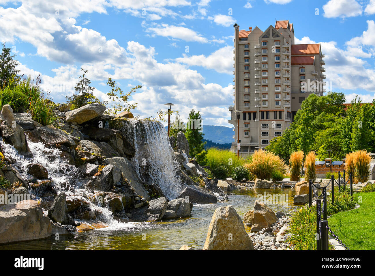 A large pond with waterfall inside the public McEuen Park near resorts and Tubbs Hill in the lakefront town of Coeur d'Alene, Idaho. Stock Photo