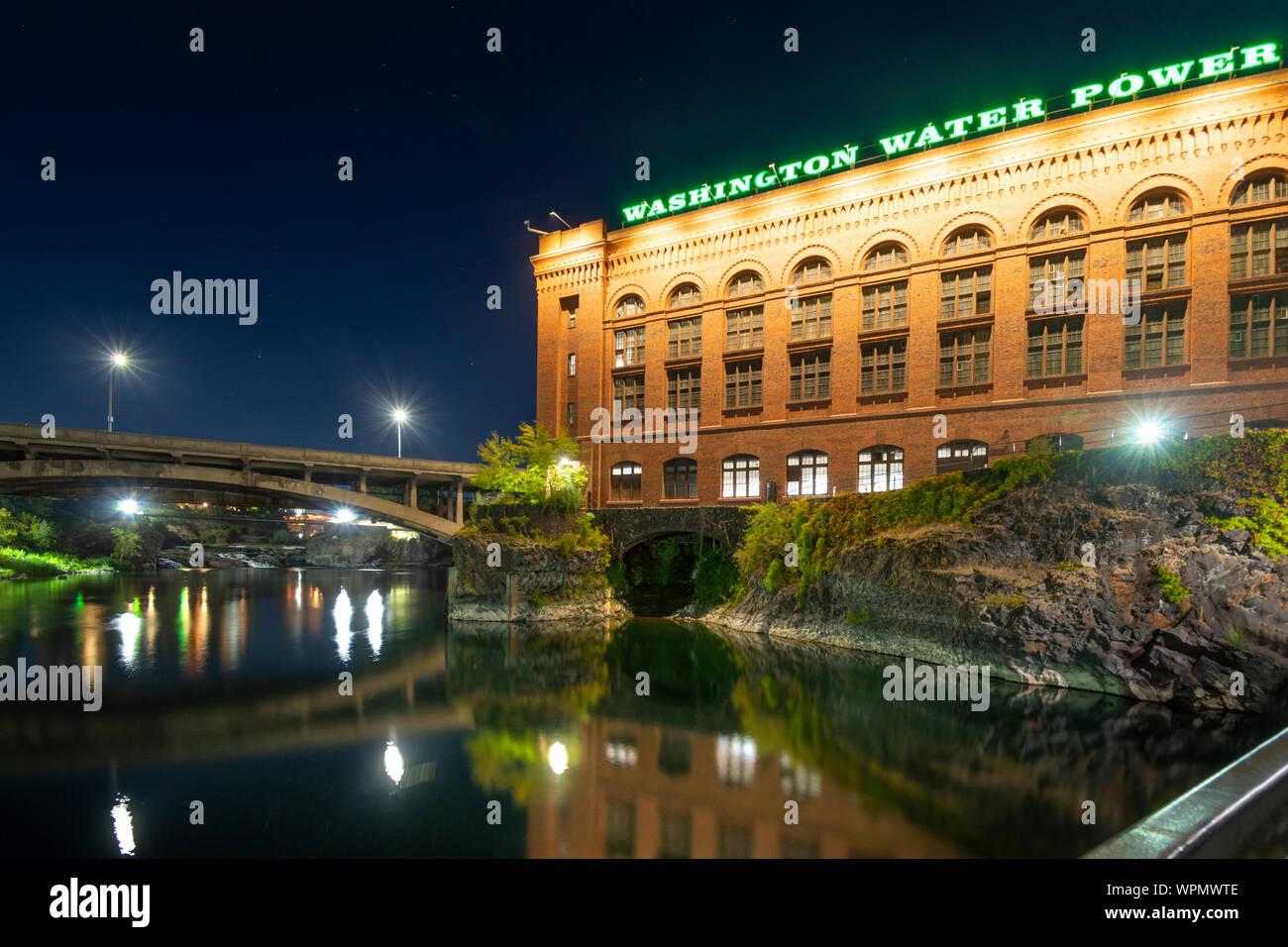 The Washington Water and Power building shines above the Spokane River and Dam near Riverfront Park at night in Spokane, Washington, USA Stock Photo