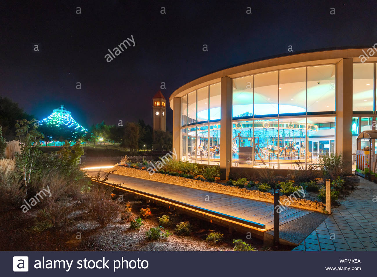 The illuminated Looff Carousel shines with the newly refurbished Spokane Pavilion in the distance in Spokane Washington's Riverfront Park Stock Photo