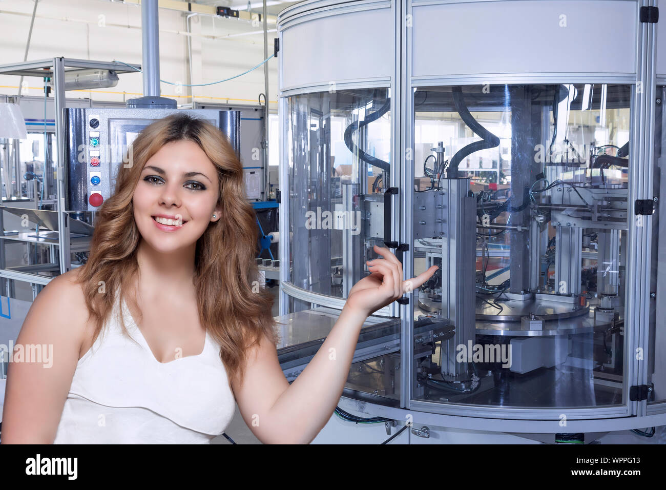 Smiling long haired young woman is showing automatic production line in the interior of an industrial plant. All potential trademarks are removed. Stock Photo