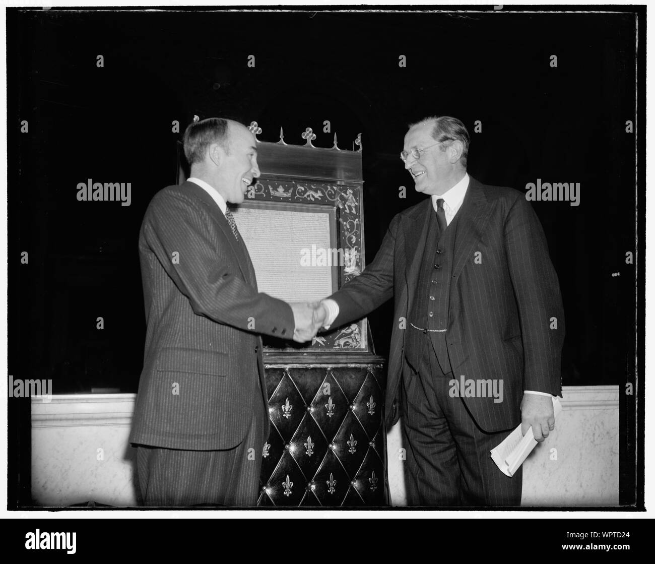 Magna Carta deposited in Congressional Library for duration of war. Washington, D.C., Nov. 28. The most cherished existing copy of the Magna Carta was today deposited in the Congressional Library here for the duration of the war by British Ambassador Lord Lothian. Librarian Archibald MacLeish, left, is shown thanking Lord Lothian after accepting the document which can be seen in the background. The Magna Carta will be on display for the public in a spot opposite the Declaration of Independence and the Constitution Stock Photo