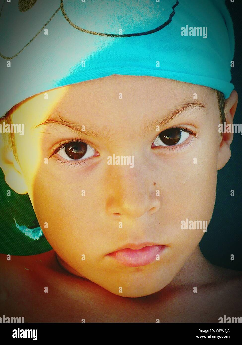 Close-up Portrait Of Serious Boy Wearing Turquoise Headwear Stock Photo