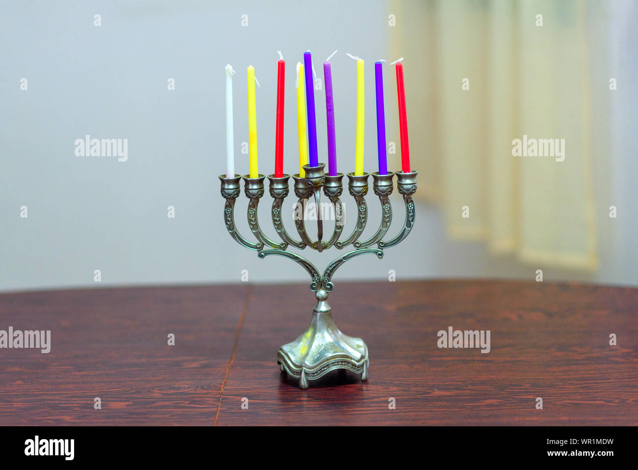 Jewish holiday Hanukkah background with menorah and colorful candles on wooden table in home. Cozy image menorah ready for lighting. Stock Photo