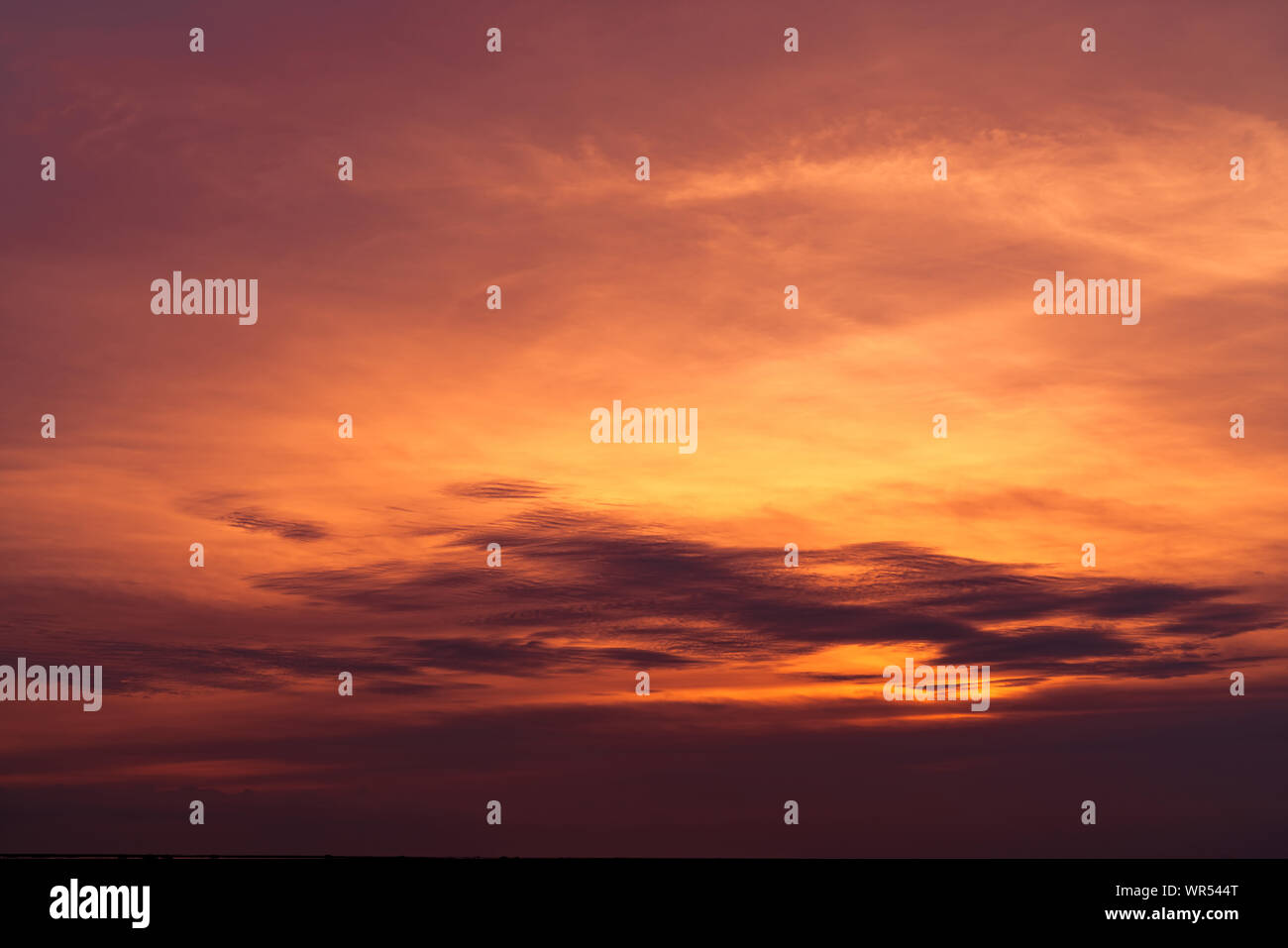 Beautiful sunset sky. Golden sky at sunset. Art picture of sky and dark clouds at dusk. Peaceful and tranquil concept. Twilight sky in evening. Stock Photo