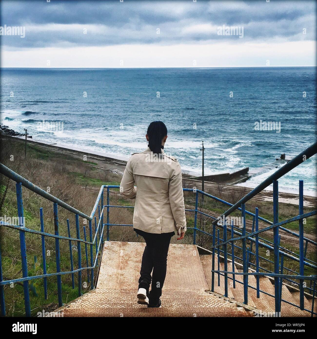 Full Length Rear View Of Woman Walking On Steps Leading Towards Sea Against Sky Stock Photo