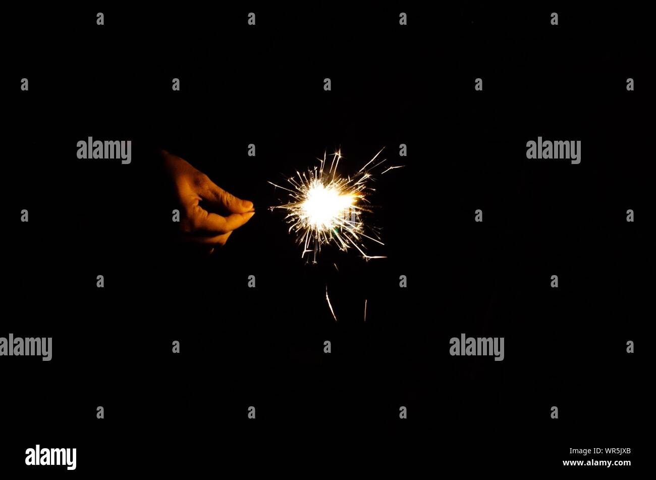 Close-up Of Hand Holding Diwali Cracker Over Black Background Stock Photo