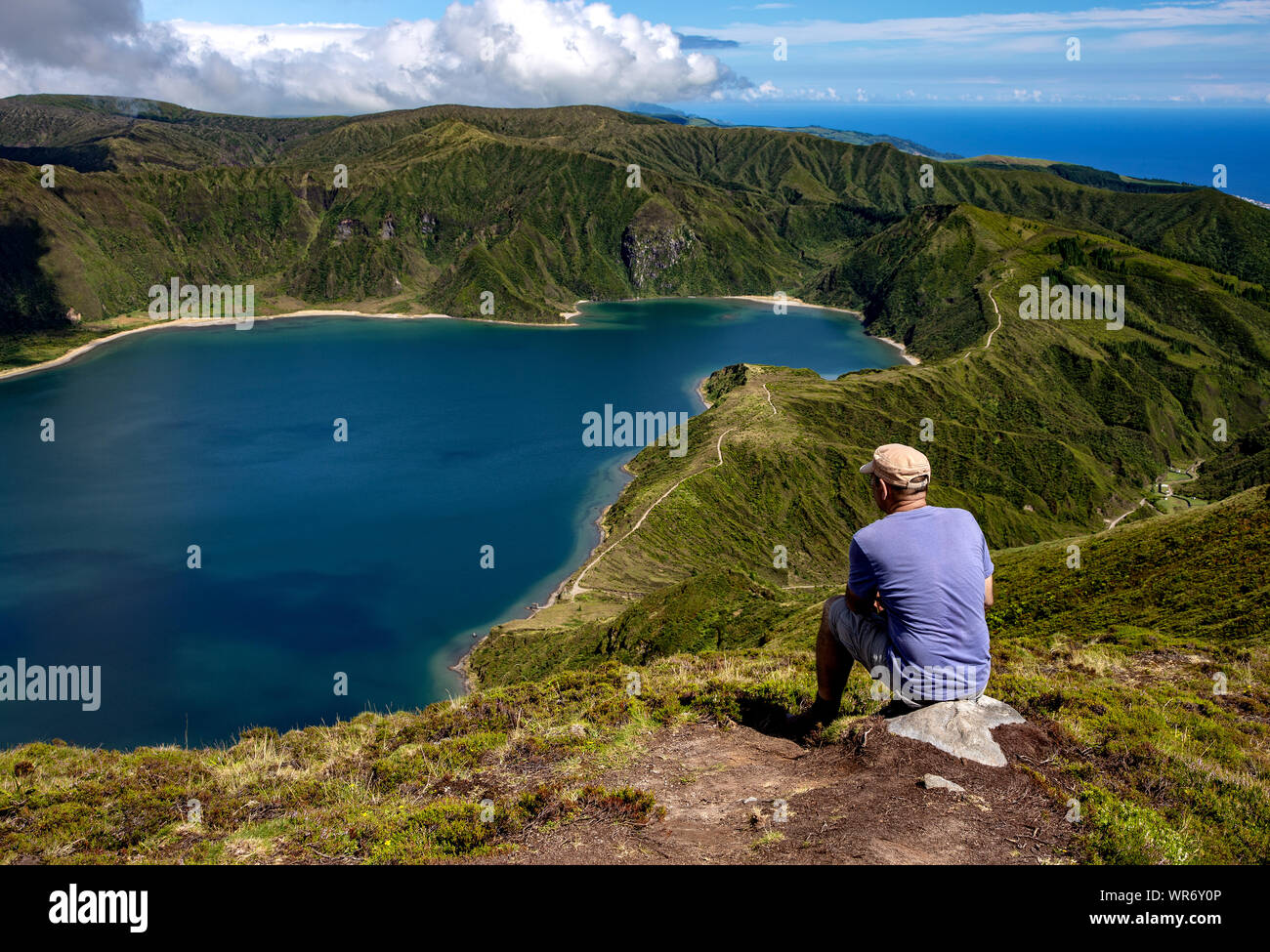 Man sitting on stone and looking towards the lake, Lagoa Fogo, Lake of Fire, São Miguel Island, Azores, Portugal, Europe. Stock Photo