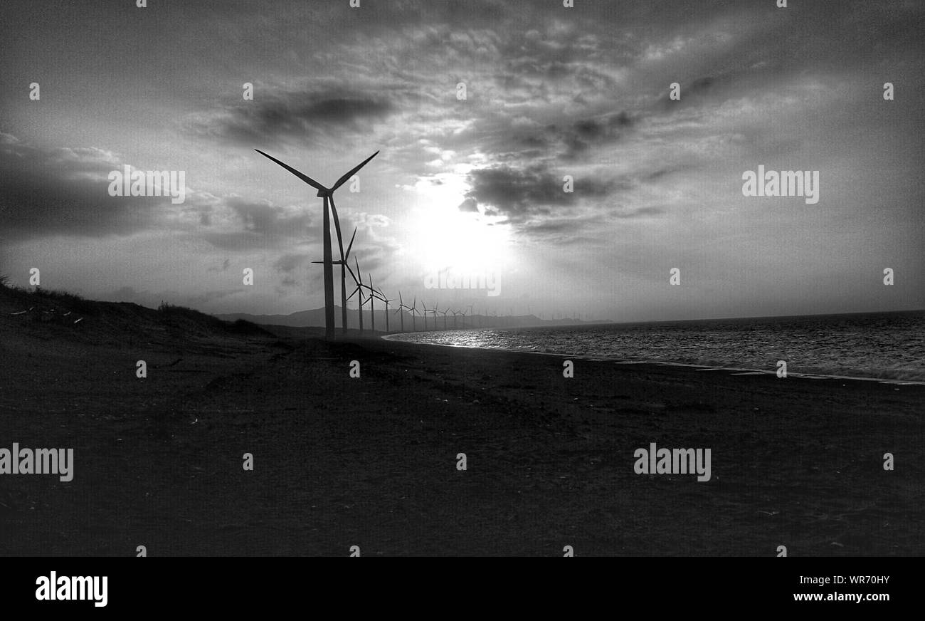 Wind Turbines On Calm Beach Against Sky Stock Photo