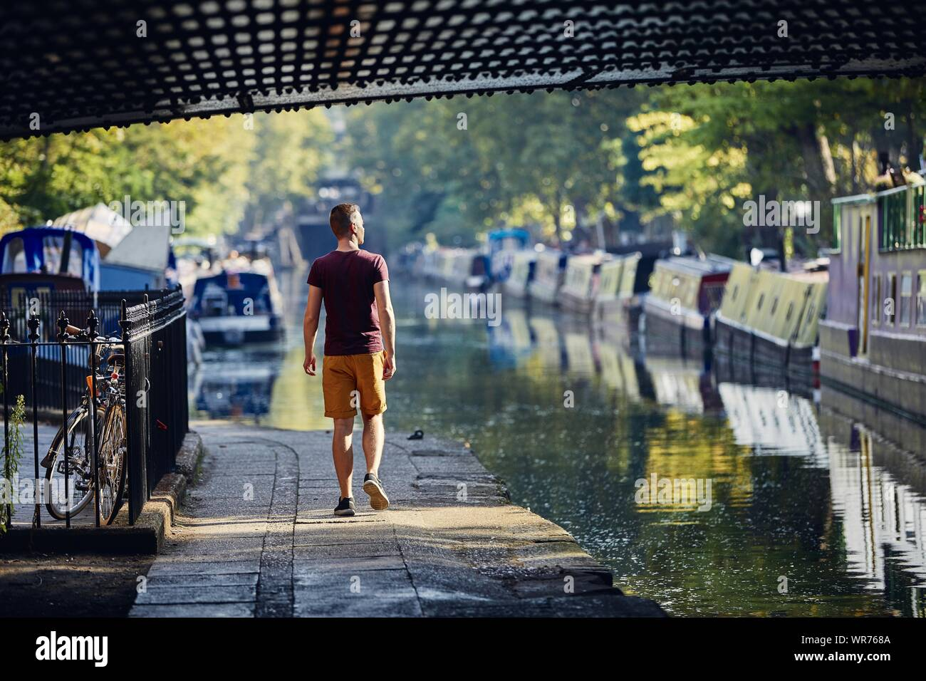Young man walking on waterfront of Regents canal with boats. Little Venice in London, United Kingdom. Stock Photo