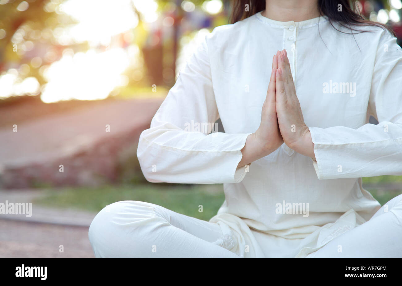 Close up of woman hands in namaste. Meditation on the background of the temple and nature. Yoga classes in a retreat center. Stock Photo