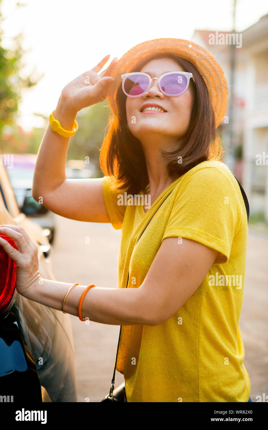 traveller woman toothy smiling face happiness emotion standing on back of suv car ready for road trip on vacation time Stock Photo