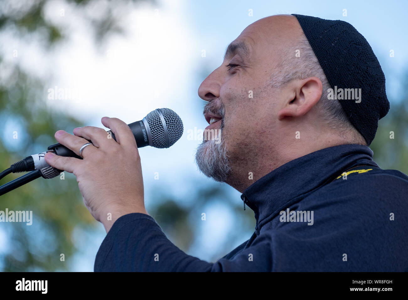 Close up of musician Daniel Jonas of 3yin singing and playing guitar at an annual concert of Jewish Klezmer music in Regent`s Park in London UK. Stock Photo