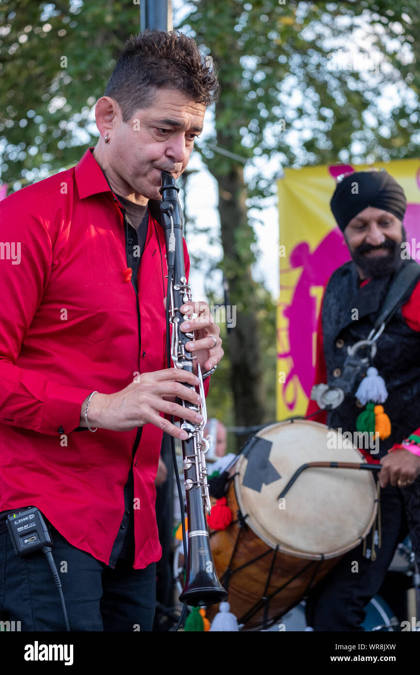 Clarinetist Merlin Shepherd playing concert of Jewish Klezmer music in Regent`s Park London UK. Drummer Jonny Kalsi from the Dhol Foundation at back Stock Photo