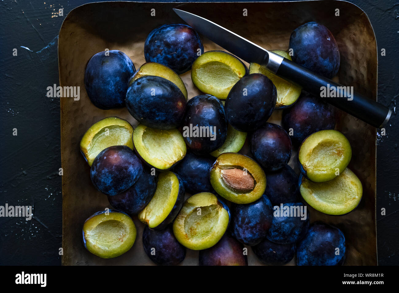 Top down view of sliced fresh blue plums and knife on a metal tray, closeup view, horizontal orientation Stock Photo