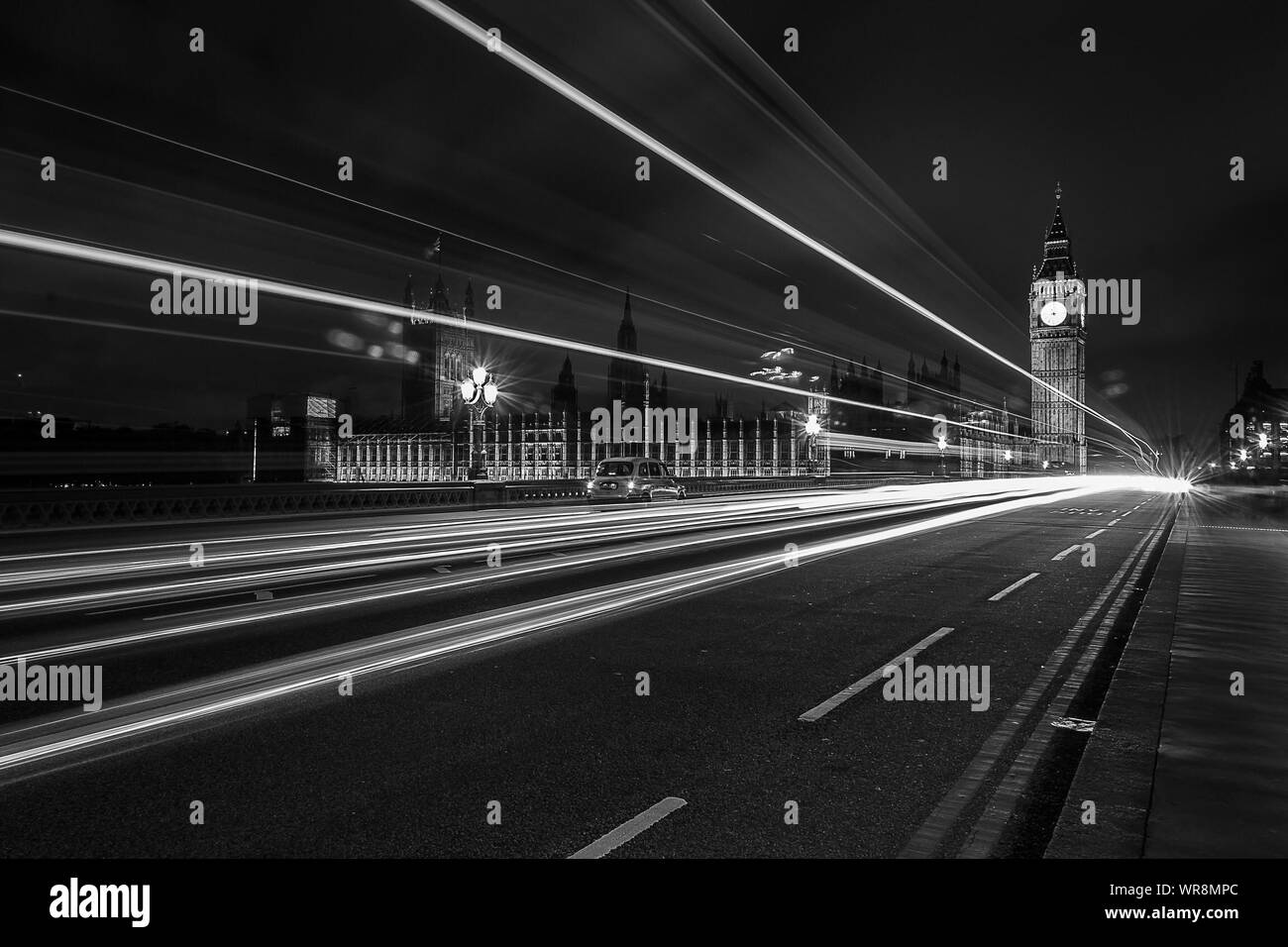 Light Trails On Westminster Bridge Against Illuminated Big Ben At Night Stock Photo